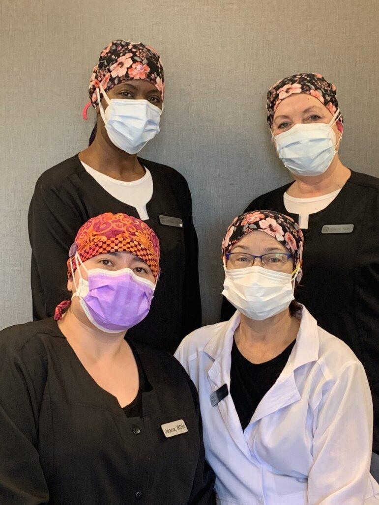 four team members wearing masks